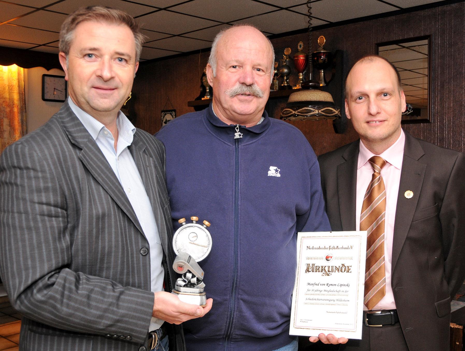 Marcin Kuczera (links) und Roman Steinbarth ehren den Unparteiischen Manfred von Rymon-Lipinski für 30jährige aktive Schiedsrichtertätigkeit. Foto: Neumann
