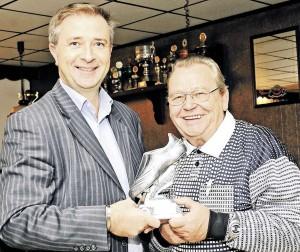 Ehrung für 50-jährige Schiedsrichtertätigkeit: Der Kreisschiedsrichterobmann Marcin Kuczera ehrt Joachim Rustenbeck (rechts) mit dem silbernen Fußballschuh. Foto: Burghard Neumann